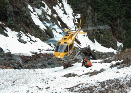 Helicopter landing on a mountain landscape near members of a rescue team.