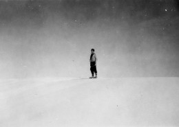 Distant view of a man standing on snow-covered hill with a stark background.