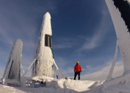 Man standing next to large radio towers covered with snow.