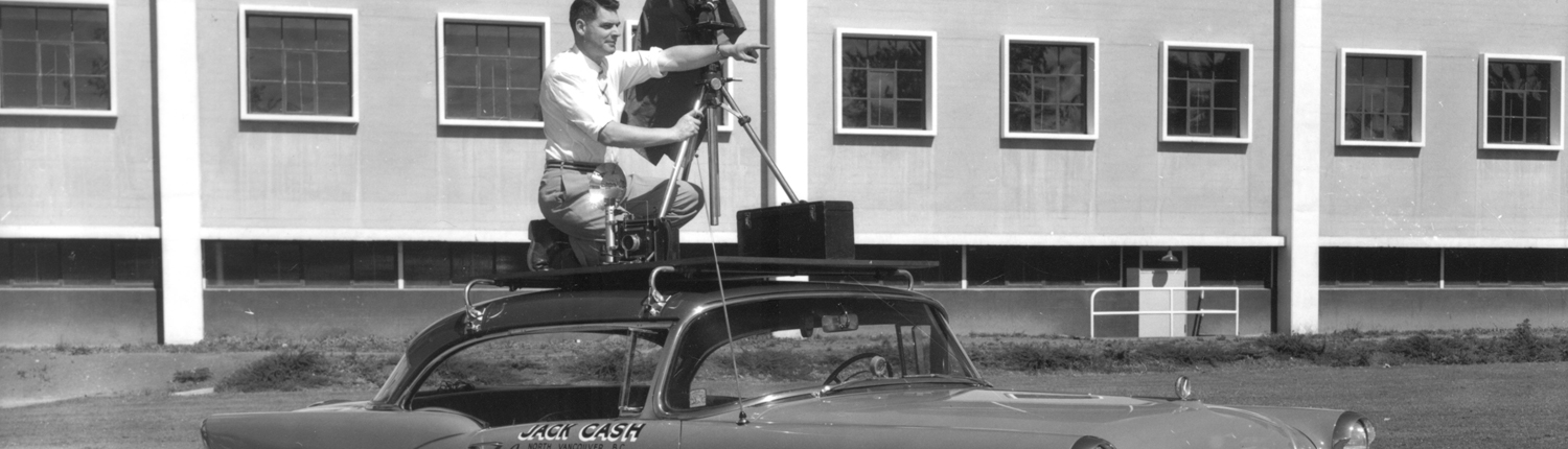 Photographer Jack Cash and camera/tripod mounted on top of Buick automobile. On door: Jack Cash Commercial Photographer plus 24 names of customers (companies).