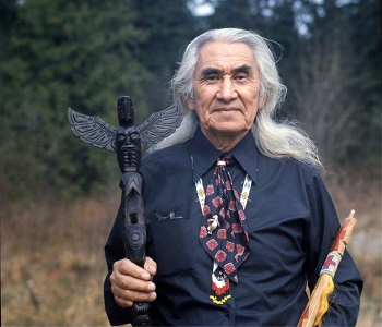 First Nations Chief Dan George poses with carvings.