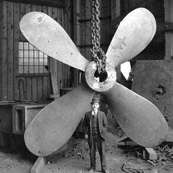 man wearing an early 1900's suit and bowler hat stands in front of a huge ship's propeller at the shipyards in North Vancouver.