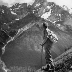 Woman hiker with rucksack stands on a ridge and looks out at the majestic mountain range in the background.