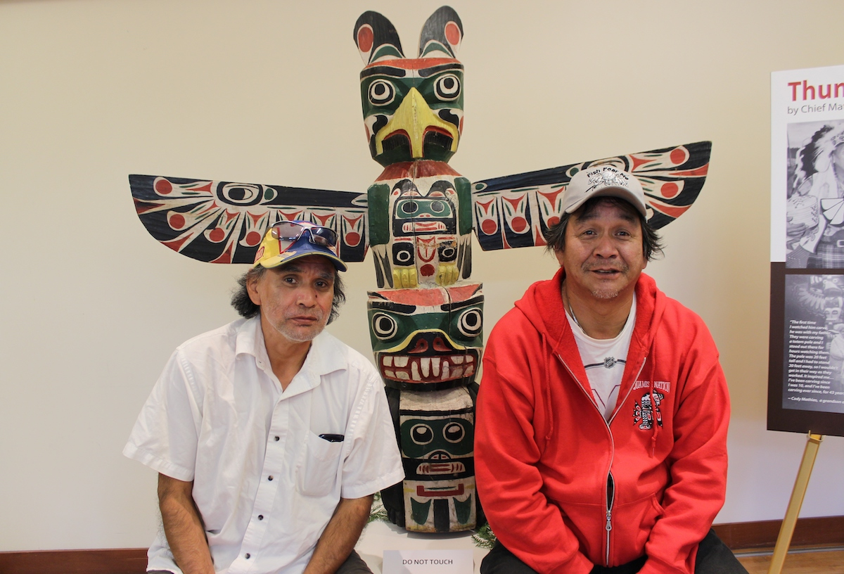 Cody Mathias (right) with cousin Vern Joseph (left) in front of Thunderbird totem pole carved by Chief Mathias Joe. The NVMA acquired this Thunderbird pole in 2014 thanks to a generous donation by Don Reid. The pole represents the story of Chief Mathias Joe's family, who originated from a Thunderbird Chief. In 2015 members of Chief Mathias Joe's family held a welcome ceremony for the Thunderbird pole at the NVMA.
