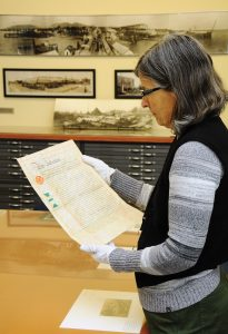 Our former archivist, Janet Turner, looking at a legal document for the adoption of a baby girl in 1910. Photo: Cindy Goodman, North Shore News