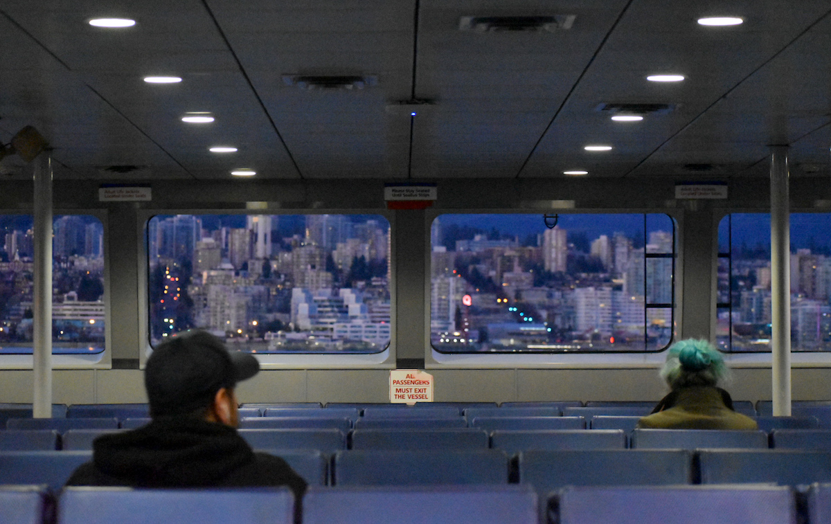 Image of two people on a very empty Seabus in April 2020. Photo: Jackson Waller