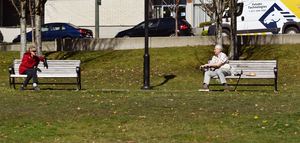 Two people talking to each other on two separate benches to ensure safe physical distancing. Photo: Jackson Waller