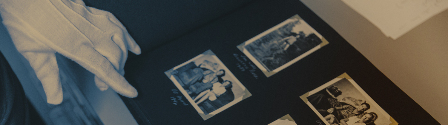 The white gloved hand of an archivist points to family snapshots arranged in a black paged photo album.