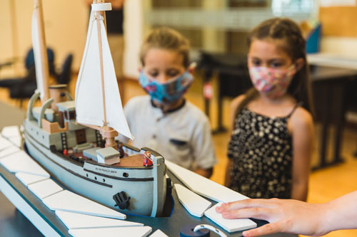 Two kids wearing COVID-19 protection masks over their mouths while viewing a museum demonstration of a wooden model ship.