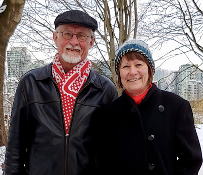 Modern day, middle-aged couple wrapped in winter coats, hats and scarves, poses outside at an urban park with bare trees in the background and high rises in the distance.