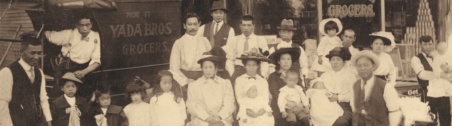 Group of about 15 members of the Yada family, young and old, posing in front of their grocery store and store truck. This Asian immigrant family is dressed in traditional 1916 Western attire of white button-up shirts, hats, suit vests and coats for the men, and white blouses, elaborate large hats and long skirts for the women.