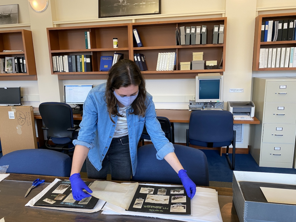 Archives and Community Engagement Intern Nina Patterson preserving one of Neal Carter's albums, March 2021.