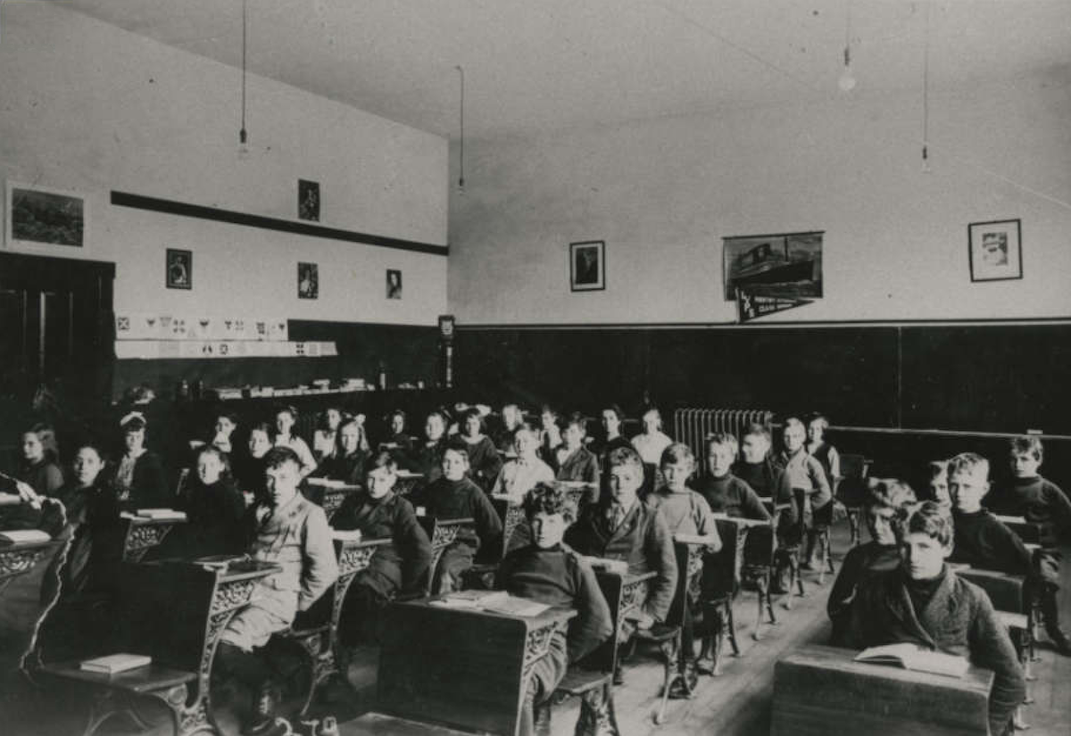 Pupils in Lynn Valley School class room. Vera Fromme, third from left. Alec Allan, first row at right. NVMA 6983
