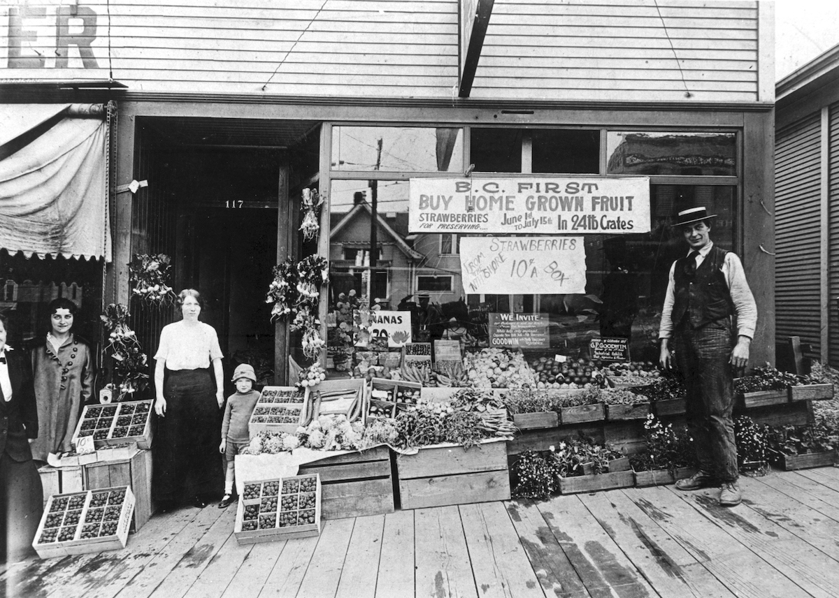 NVMA 5030 - G.F. Goodwin, Fruiterer and Green Grocer, 117 Lonsdale. Mrs. Ada Goodwin and son George in doorway. Mr. George Flower Goodwin at right, ca. 1916.