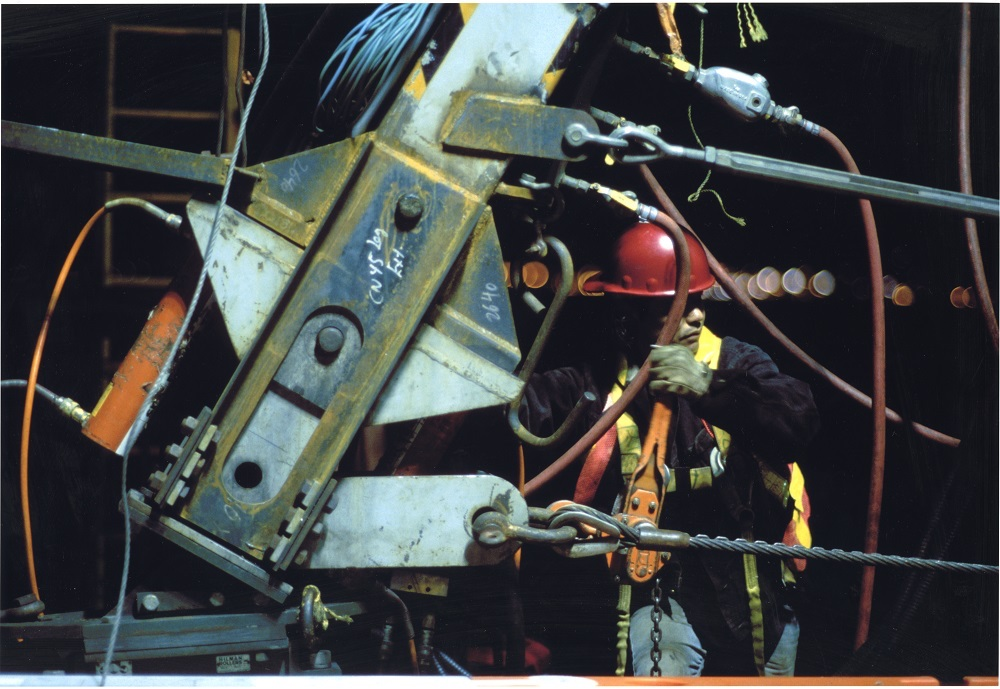 Lions Gate Bridge reconstruction, 2001. The bottom portion of the leg of the jacking traveler was retractable. In this photo, preparations are being made to lower the leg onto the bridge deck. During deck replacement operations, the traveler was suspended by arms attached to the bridge hangers. To move the traveler, the leg was extended by hydraulic jacks to rail beams on the bidge's sidewalks. NVMA 14474