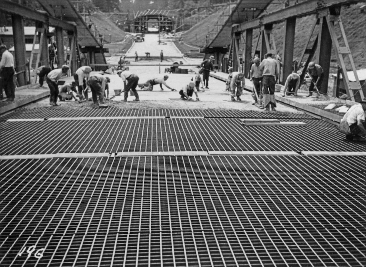 Here is a long view of the deck of the Lions Gate Bridge, steel Tee-grid in foreground, and workers laying in concrete surface of the road bed. NVMA 5292.