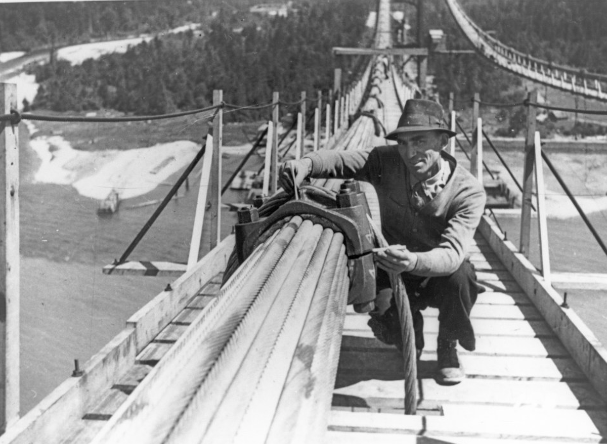 A close-up showing a worker with the clamping mechanism used on the suspension cables of the Lions Gate Bridge. The worker is crouched on the catwalk used for installing the cables, 1938. NVMA, 5295.